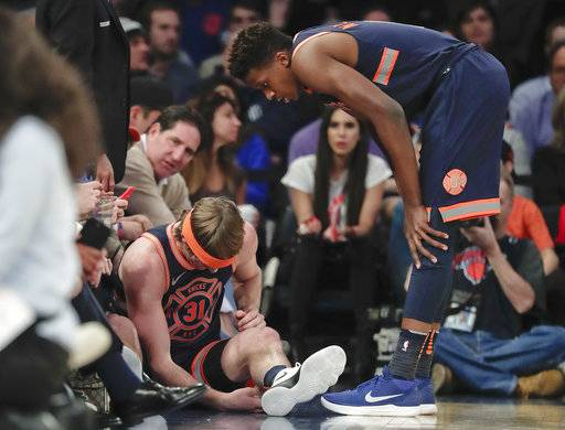 New York Knicks guard Ron Baker (31) sits on the sideline with an injury to his right arm as guard Frank Ntilikina (11) looks on during the first quarter of an NBA basketball game against the Brooklyn Nets, Tuesday, Jan. 30, 2018, in New York.
