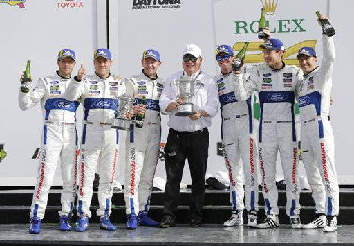 FILE - In this Sunday, Jan. 28, 2018, file photo, team owner Chip Ganassi, center, celebrates with his drivers, from left, Sebastien Bourdais, of France, Dirk Mueller, of Germany, Joey Hand, Scott Dixon, of New Zealand, Richard Westbrook, of Great Britain and Ryan Briscoe, of Australia, after they placed first and second in the GT LeMans class in the IMSA 24-hour auto race at Daytona International Speedway, in Daytona Beach, Fla. Ganassi's two cars destroyed the GT Le Mans class at Rolex 24 of Daytona to give the organization its 200th overall victory. The team owner is not basking in the glory of his accomplishment. He's ready to move on to the next race.