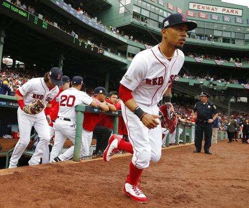 FILE - In this Oct. 9, 2017, file photo, Boston Red Sox's Mookie Betts runs onto the field for Game 4 of baseball's American League Division Series against the Houston Astros in Boston. Betts and the Red Sox have argued the first salary arbitration case of the year, with the All-Star outfielder asking for a raise from $950,000 to $10.5 million and the team offering $7.5 million. Arbitrators Dan Brent, Mark Burstein, Phillip LaPorte heard arguments Tuesday, Jan. 30, 2018, and a decision is expected Wednesday.