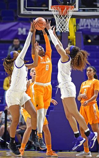 Tennessee guard Rennia Davis (0) battles for a rebound between LSU forward Raven Farley, left, and forward Ayana Mitchell, right, in the first half of an NCAA college basketball game, Sunday, Jan. 28, 2018, in Baton Rouge, La. LSU won 70-59.