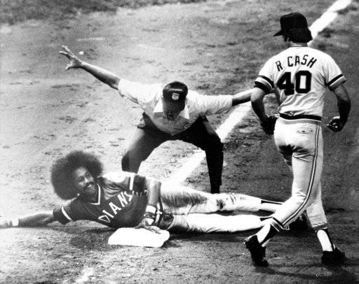FILE - In this Sept. 10, 1974, file photo, Cleveland Indians' Oscar Gamble flashes a smile after sliding safely into third in the sixth inning of baseball game against the Detroit Tigers in Cleveland, Ohio, Sept. 10, 1974. Gamble doubled and made it to third on an outfield error. Detroit's Ron Cash watches as umpire Bill Kunkel flashes the safe signal. Gamble, an outfielder who hit 200 home runs over 17 major league seasons, died Wednesday, Jan. 31, 2018, of a rare tumor of the jaw. He was 68.