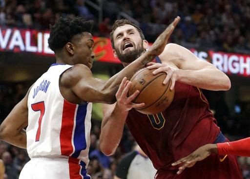 Detroit Pistons' Stanley Johnson, left, fouls Cleveland Cavaliers' Kevin Love in the first half of an NBA basketball game, Sunday, Jan. 28, 2018, in Cleveland.