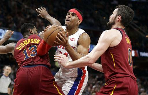 Detroit Pistons' Tobias Harris, center, drives between Cleveland Cavaliers' Tristan Thompson, left, and Kevin Love in the second half of an NBA basketball game, Sunday, Jan. 28, 2018, in Cleveland. The Cavaliers won 121-104.