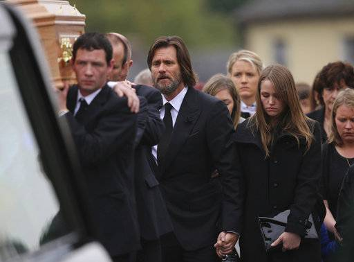 FILE- In this Oct. 10, 2015, file photo, actor Jim Carrey, center, joins mourners behind the coffin of his ex-girlfriend Cathriona White as they walk to Our Lady of Fatima Church, in her home village of Cappawhite, Co Tipperary, Ireland, ahead of her funeral. A wrongful death lawsuit filed by the husband and mother of White was dismissed on Jan. 25, 2018. Mark Burton and Brigid Sweetman sued Carrey claiming he provided the prescription drugs White used to overdose in September 2015. Coroner's officials ruled White's death a suicide.