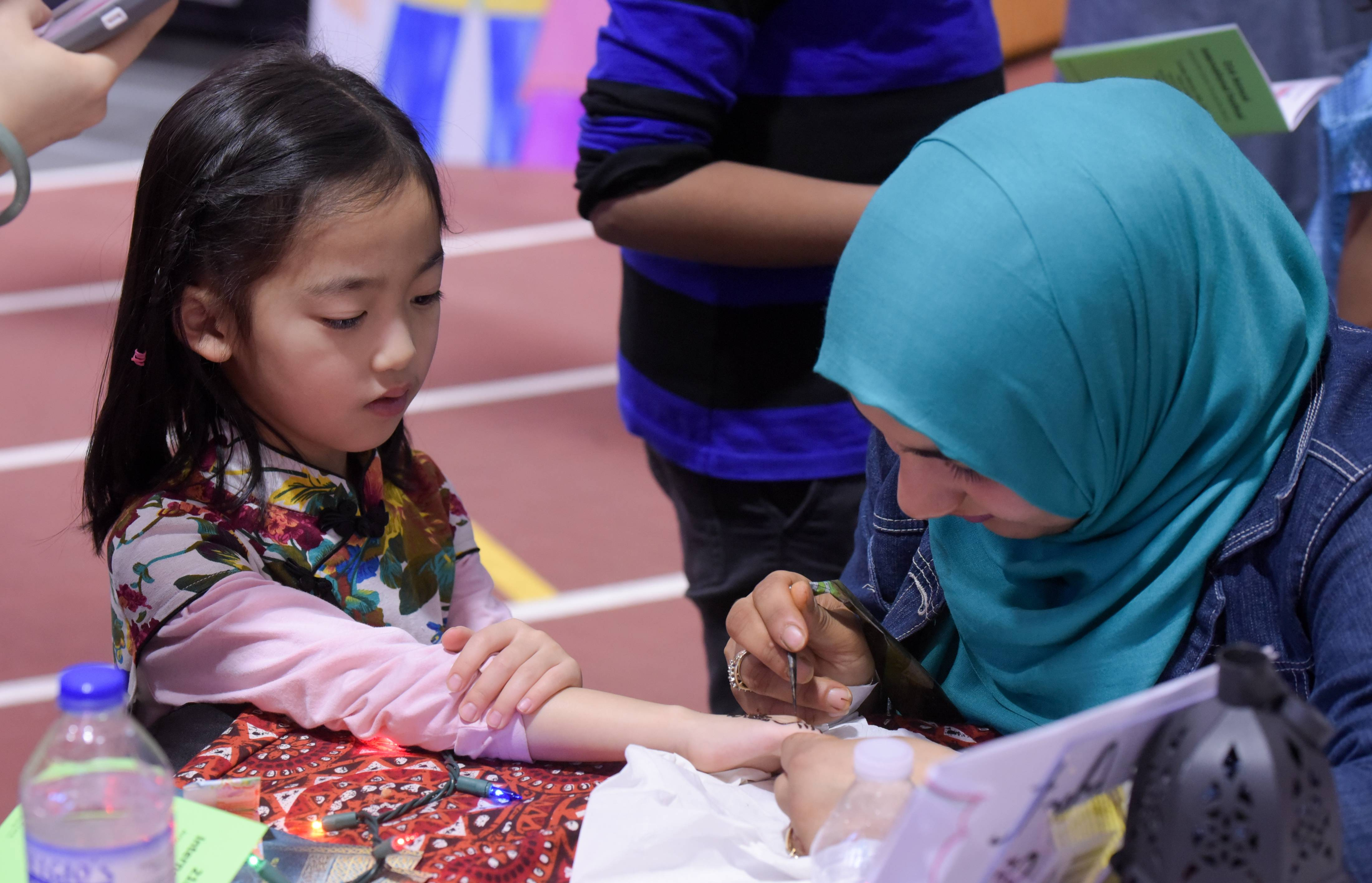 Booths at the International Festival introduce religious and ethnic traditions with hand-on activities such as henna art.
