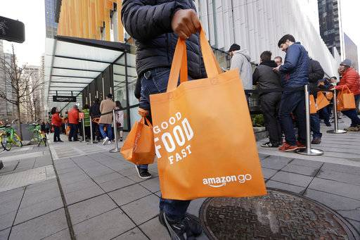 In this Monday, Jan. 22, 2018, photo, a shopper walks past others in a long line waiting to get inside an Amazon Go store in Seattle. Amazon.com, Inc. reports earnings Thursday, Feb. 1, 2018.