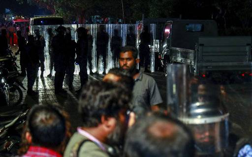 Maldivian police officers stand guard blocking a road during an opposition protest demanding the release of political prisoners in Male, Maldives, Friday, Feb. 2, 2018. Political opponents of the Maldives government clashed with police on the streets after the Supreme Court ordered the release of imprisoned politicians, including an exiled ex-president. Hundreds of people celebrated in the capital by waving the country's flag after the court overturned guilty verdicts against ex-President Mohamed Nasheed and an ex-vice president that the court said had been influenced by the government.