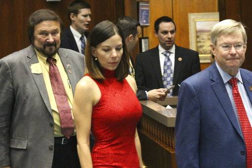Arizona state Rep. Michelle Ugenti-Rita, center, leaves the House speaker's office along with Reps. Jay Lawrence, left, and Vince Leach, right, in Phoenix, Ariz., Thursday, Feb. 1, 2018. The House is poised to consider a motion by Speaker J.D. Mesnard, (background right), to immediately expel Rep. Don Shooter following a sexual harassment investigation prompted by Ugenti-Rita's October complaint against him.