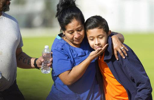 People pick up students after a shooting at the Salvador B. Castro Middle School near downtown Los Angeles Thursday, Feb. 1, 2018. A girl opened fire Thursday in a middle school classroom on Thursday, authorities said.