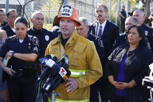 Los Angeles Fire department spokesman Erik Scott, center briefs the media outside the Belmont High School in Los Angeles Thursday, Feb. 1, 2018. Two students were shot and wounded, one critically, inside a Los Angeles middle school classroom Thursday morning and police arrested a female student believed to be 12 years old, authorities said. At right, Mónica García, Los Angeles Uinfied School District Board Member.