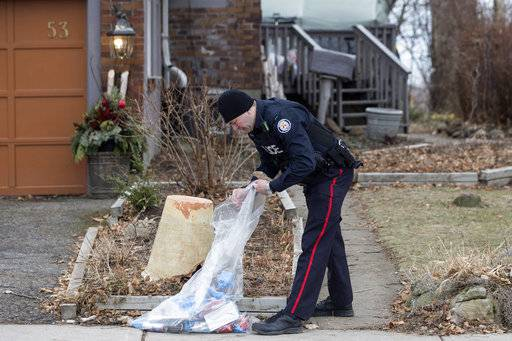 In this Jan. 29 , 2018 photo, a police officer investigates outside a home on Mallory Crescent in Toronto, Canada where Bruce McArthur did landscape work. The burly landscaper is suspected of being a serial killer whose alleged deeds have set police on a grim search for clues that may be hidden in plain sight across Canada's largest city. (Chris Young/The Canadian Press via AP)