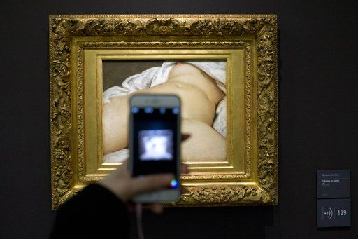 "FILE - In this Feb.12 2016 file photo, a visitor takes a picture of Gustave Courbet's 1866 ""The Origin of the World,"" at Musee d'Orsay museum, in Paris. A French teacher, whose Facebook account was suspended in 2011 after he posted a photo of a famous 19th-century nude painting, is suing Thursday Feb. 1, 2018 the California-based social network Facebook for alleged ""censorship"". Frederic Durand-Baissas, a 59-year-old Parisian teacher and art lover, posted a photo of ""The Origin of the World,"" which depicts female genitalia."