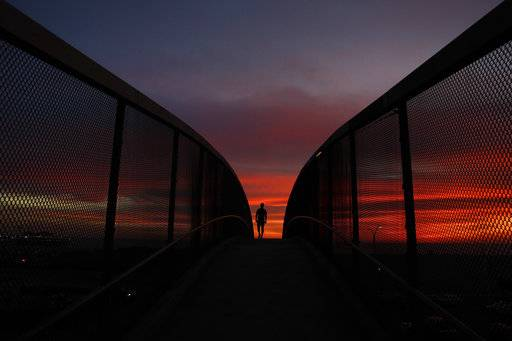 FILE - In this Jan. 16, 2018 file photo, Mark Waissar, 49, is silhouetted against sunset as he walks on an overpass above the Pacific Coast Highway in Santa Monica, Calif. California's water managers are carrying out their mid-winter snowpack survey Thursday, Feb. 1, 2018, as the winter's dry spell persists. Some Southern California areas including Los Angeles have received only one significant rain in months, and that rain, in January, caused deadly mudslides.