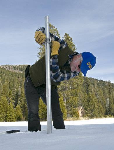 Frank Gehrke, chief of the California Cooperative Snow Surveys Program for the Department of Water Resources, checks the snowpack depth as he conducts the second snow survey of the season Thursday, Feb. 1, 2018, near Echo Summit, Calif. The snow survey showed the snow pack at this location at 13.6 inches of deep with a water content of 2.6 inches.