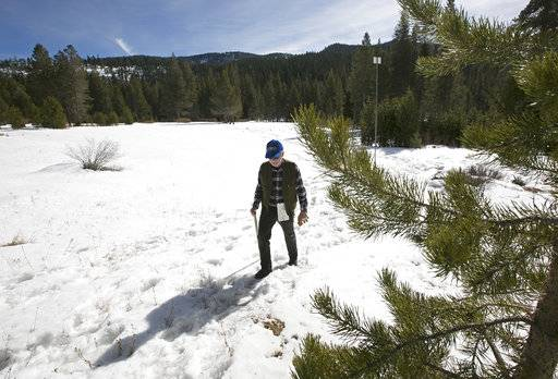 Frank Gehrke, chief of the California Cooperative Snow Surveys Program for the Department of Water Resources, leaves a snow covered meadow after conducting the second snow survey of the season Thursday, Feb. 1, 2018, near Echo Summit, Calif. The snow survey showed the snow pack at this location at 13.6 inches of deep with a water content of 2.6 inches.