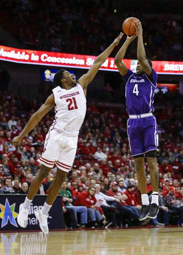 Northwestern's Vic Law (4) shoots against Wisconsin's Khalil Iverson (21) during the first half of an NCAA college basketball game Thursday, Feb. 1, 2018, in Madison, Wis.