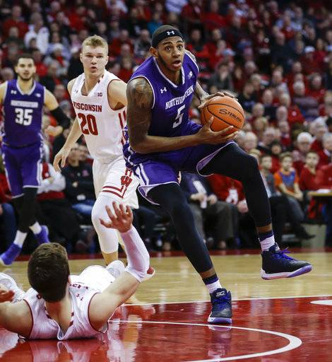 Northwestern's Dererk Pardon (5) drives past Wisconsin's Ethan Happ, lying on the court, during the first half of an NCAA college basketball game Thursday, Feb. 1, 2018, in Madison, Wis.