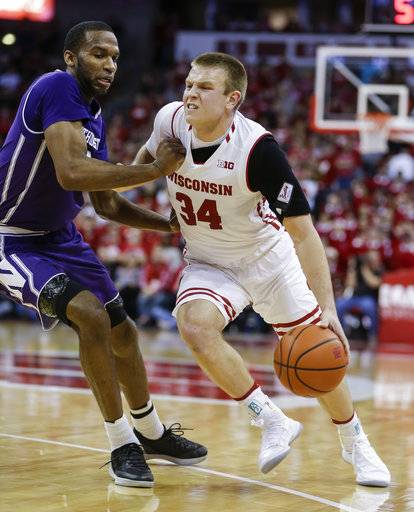 Wisconsin's Brad Davison (34) drives against Northwestern's Vic Law during the second half of an NCAA college basketball game Thursday, Feb. 1, 2018, in Madison, Wis. Northwestern won 60-52.