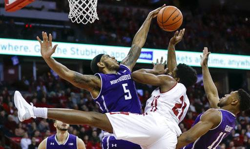 Northwestern's Dererk Pardon (5) blocks a shot by Wisconsin's Khalil Iverson (21) during the second half of an NCAA college basketball game Thursday, Feb. 1, 2018, in Madison, Wis. At right is Northwestern's Anthony Gaines (11). Northwestern won 60-52.