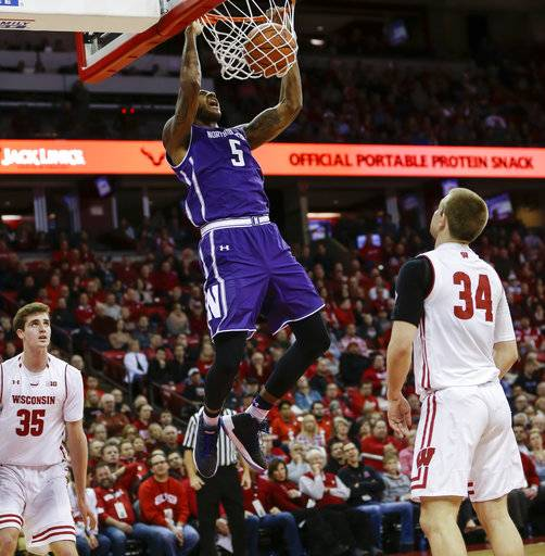 Northwestern's Dererk Pardon (5) dunks betweem Wisconsin's Nate Reuvers (35) and Brad Davison (34) during the first half of an NCAA college basketball game Thursday, Feb. 1, 2018, in Madison, Wis.