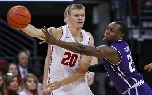 Wisconsin's T.J. Schlundt (20) passes the ball as Northwestern's Scottie Lindsey defends during the first half of an NCAA college basketball game Thursday, Feb. 1, 2018, in Madison, Wis.