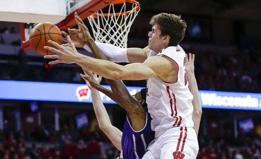 Wisconsin's Ethan Happ fouls Northwestern's Dererk Pardon, left, during the first half of an NCAA college basketball game Thursday, Feb. 1, 2018, in Madison, Wis.