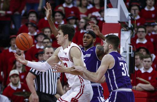 Wisconsin's Ethan Happ, left, works to control of the ball against Northwestern's Dererk Pardon, behind, and Bryant McIntosh, right, during the first half of an NCAA college basketball game Thursday, Feb. 1, 2018, in Madison, Wis.