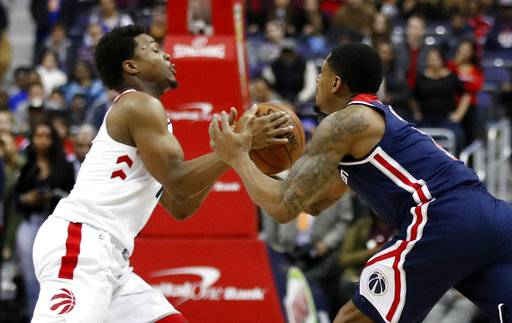 Toronto Raptors guard Kyle Lowry, left, and Washington Wizards guard Bradley Beal go for the ball during the second half of an NBA basketball game Thursday, Feb. 1, 2018, in Washington. The Wizards won 122-119.