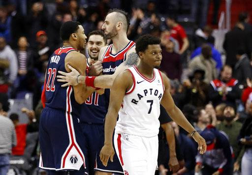 Washington Wizards forward Otto Porter Jr., left, forward Tomas Satoransky, from the Czech Republic, and center Marcin Gortat, from Poland, celebrate, as Toronto Raptors guard Kyle Lowry (7) heads off the court after an NBA basketball game Thursday, Feb. 1, 2018, in Washington. The Wizards won 122-119.