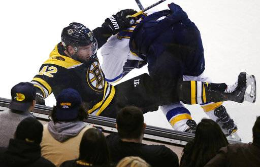 Boston Bruins right wing David Backes (42) is dropped to the ice on a hard check by St. Louis Blues center Brayden Schenn during the third period of an NHL hockey game in Boston, Thursday, Feb. 1, 2018. The Bruins defeated the Blues 3-1.