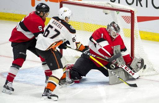 Ottawa Senators goaltender Mike Condon knocks away a shot from Anaheim Ducks center Rickard Rakell under pressure from defenseman Cody Ceci during the first period of an NHL hockey game Thursday, Feb. 1, 2018, in Ottawa, Ontario. (Adrian Wyld/The Canadian Press via AP)
