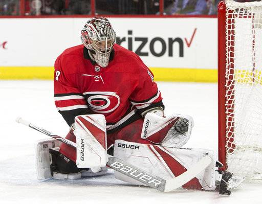 Carolina Hurricanes' goalie Cam Ward guides the puck past the net during the first period of an NHL hockey game against the Montreal Canadiens in Raleigh, N.C., Thursday, Feb. 1, 2018.