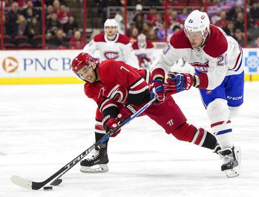 Carolina Hurricanes' Derek Ryan (7) and Montreal Canadiens' Nicolas Deslauriers (20) fight for the puck during the first period of an NHL hockey game in Raleigh, N.C., Thursday, Feb. 1, 2018.