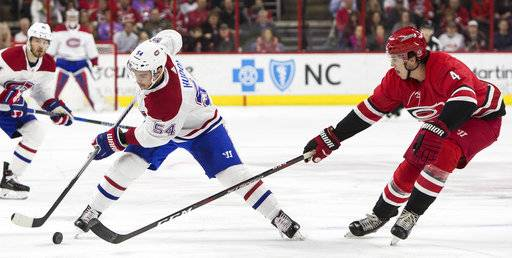 Montreal Canadiens' Charles Hudon (54) handles the puck against the defense of Carolina Hurricanes' Haydn Fleury (4) during the first period of an NHL hockey game in Raleigh, N.C., Thursday, Feb. 1, 2018.
