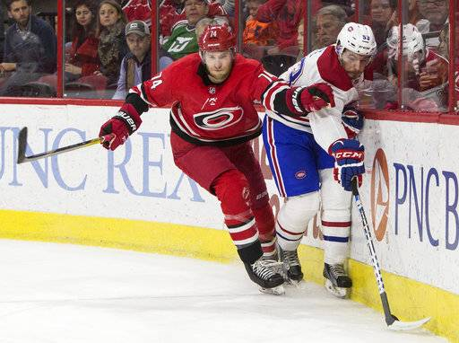 Montreal Canadiens' Victor Mete (53) reaches for the puck ahead of Carolina Hurricanes' Jaccob Slavin (74) during the first period of an NHL hockey game in Raleigh, N.C., Thursday, Feb. 1, 2018.