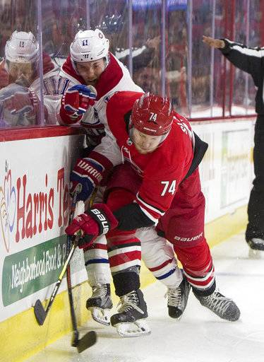 Montreal Canadiens' Brendan Gallagher (11) and Carolina Hurricanes' Jaccob Slavin (74) collide along the boards during the first period of an NHL hockey game in Raleigh, N.C., Thursday, Feb. 1, 2018.