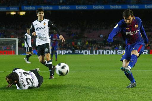 FC Barcelona's Lionel Messi, right, kicks the ball during the Spanish Copa del Rey, semifinal, first leg, soccer match between FC Barcelona and Valencia at the Camp Nou stadium in Barcelona, Spain, Thursday, Feb. 1, 2018.