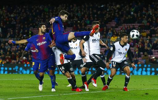 FC Barcelona's Gerard Pique, center, kicks the ball during the Spanish Copa del Rey, semifinal, first leg, soccer match between FC Barcelona and Valencia at the Camp Nou stadium in Barcelona, Spain, Thursday, Feb. 1, 2018.