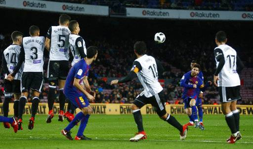 FC Barcelona's Lionel Messi, second right, shoots a free kick during the Spanish Copa del Rey, semifinal, first leg, soccer match between FC Barcelona and Valencia at the Camp Nou stadium in Barcelona, Spain, Thursday, Feb. 1, 2018.
