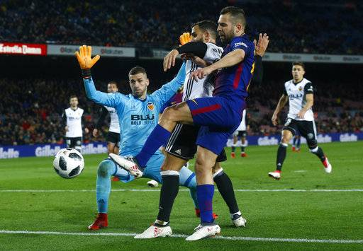 FC Barcelona's , left, duels for the ball against Valencia's during the Spanish Copa del Rey, semifinal, first leg, soccer match between FC Barcelona and Valencia at the Camp Nou stadium in Barcelona, Spain, Thursday, Feb. 1, 2018.