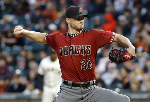 FILE - In this April 12, 2017, file photo, Arizona Diamondbacks pitcher Shelby Miller (26) throws against the San Francisco Giants during the first inning of a baseball game in San Francisco. Miller has won his salary arbitration case against Arizona after missing most of last season due to a torn elbow ligament, a decision that gave players a 2-0 record in decisions this year. Miller was awarded a $200,000 raise to $4.9 million on Thursday, Feb. 1, 2018, by arbitrators.