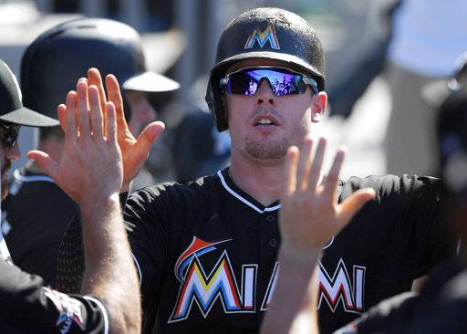 FILE - In this May 21, 2017, file photo, Miami Marlins' Justin Bour is congratulated by teammates after hitting a solo home run in the ninth inning of a baseball game against the Los Angeles Dodgers in Los Angeles. Bour went to a hearing Thursday, Feb. 1, 2018, and asked arbitrators James Oldham, Steven Wolf and Mark Burstein for a raise from $552,500 to $3.4 million. Miami offered $3 million to the 29-year-old Bour, who hit .289 last year with 25 homers and 83 RBIs. A decision is expected Friday.