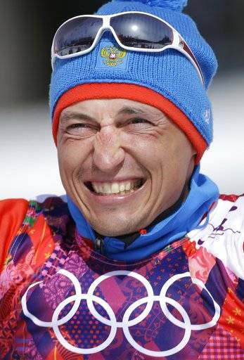 FILE - In this Feb. 23, 2014 file photo Russia's gold medal winner Alexander Legkov smiles during the flower ceremony of the men's 50K cross-country race at the 2014 Winter Olympics in Krasnaya Polyana, Russia. The Court of Arbitration for Sport ruled on Thursday, Feb. 1, 2018 to reinstate Leskov as gold medal winner of the men's 50-kilometer cross-country skiing which he was stripped of on doping allegations earlier.