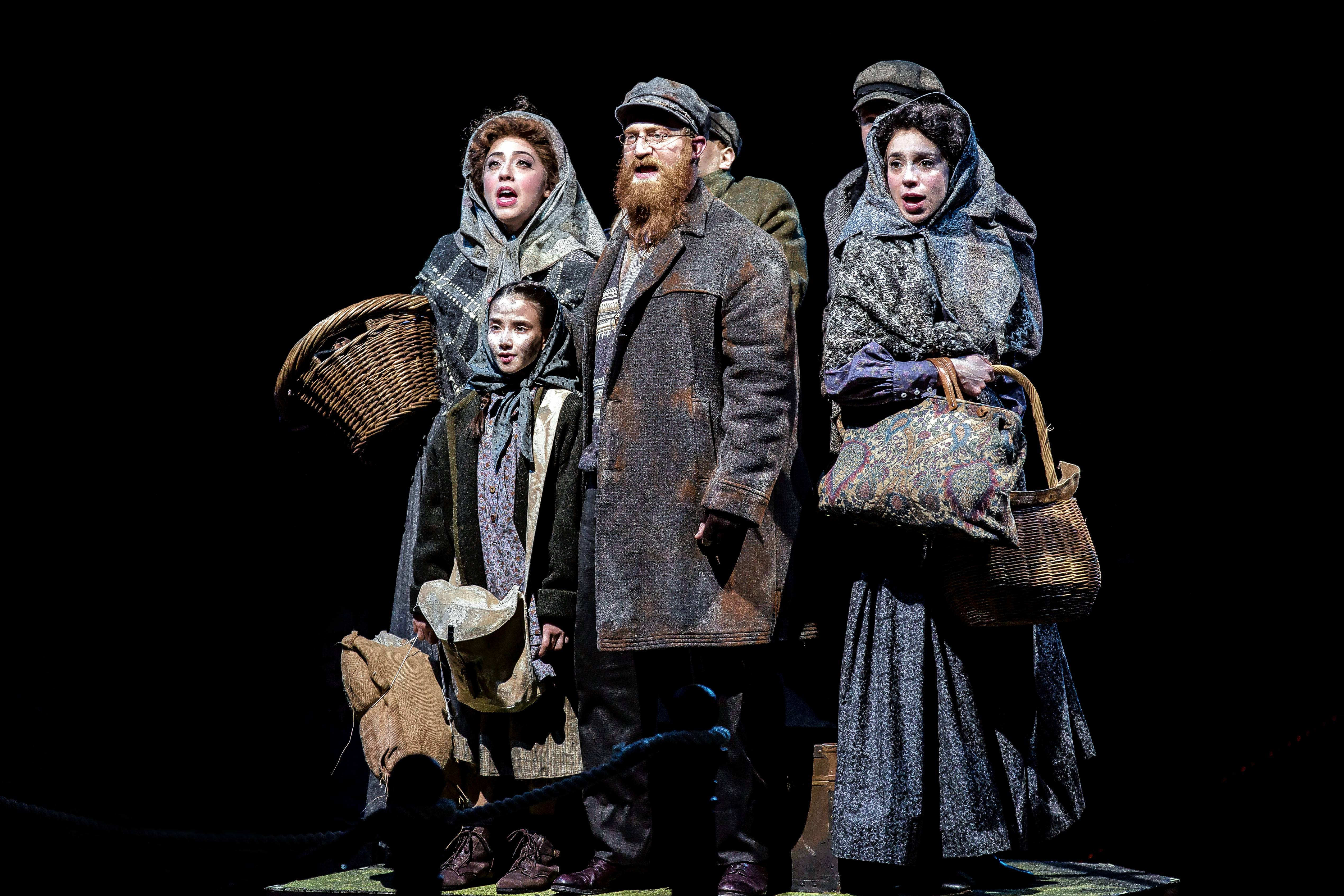 "The Little Girl (Paula Hlava), center, and her father, Tatah (Benjamin Magnuson) arrive at Ellis Island among a group of other immigrants in ""Ragtime."" The Marriott Theatre in Lincolnshire production continues through Sunday, March 18."