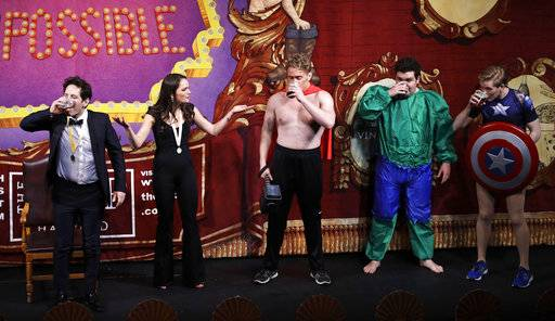 "Actor Paul Rudd, left, chugs beer with actors dressed as superhero characters during a roast at Harvard University in Cambridge, Mass., Friday, Feb. 2, 2018. Rudd was honored as ""Man of the Year"" by the Hasty Pudding Theatricals at Harvard."