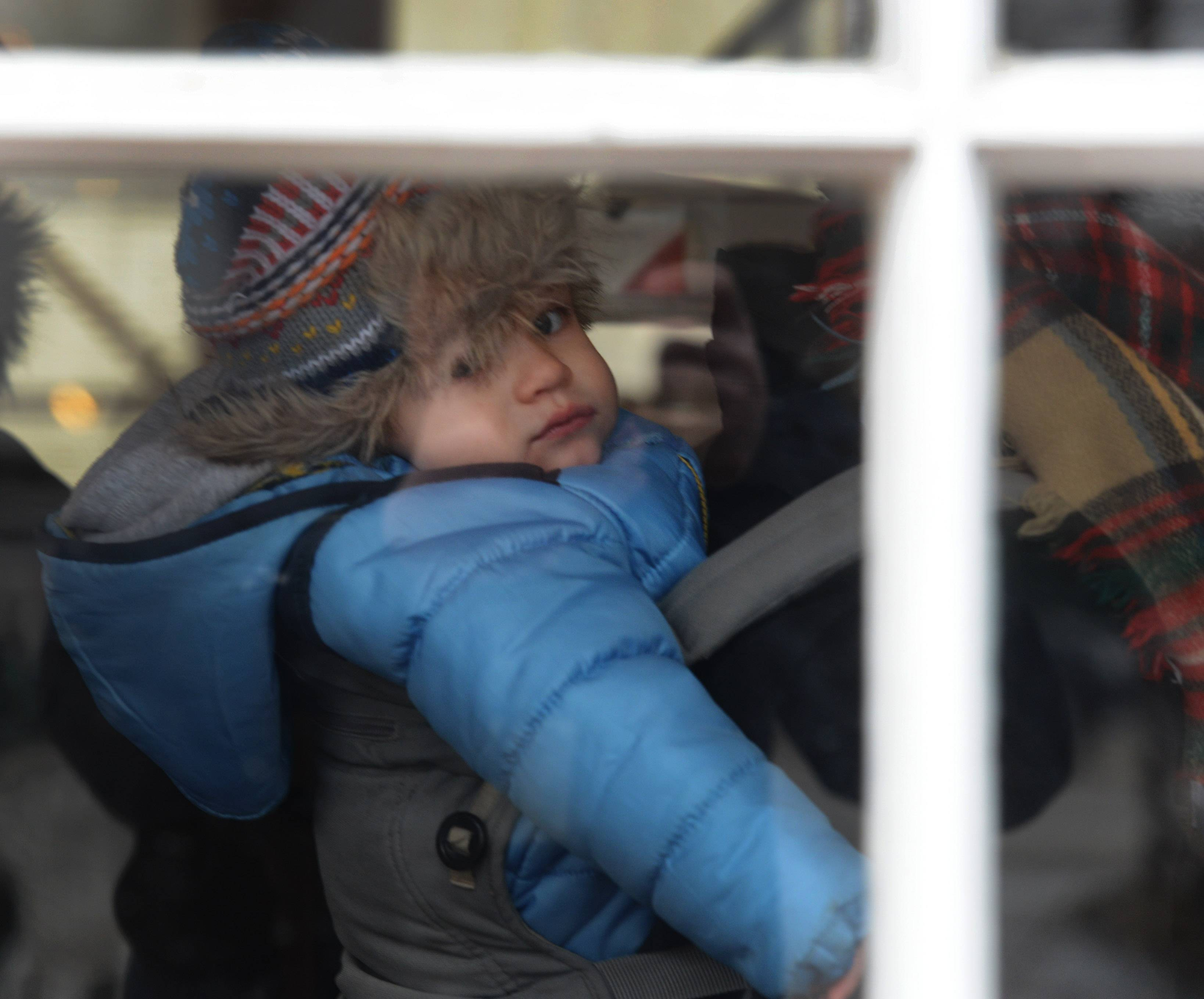 Viewed through the front window of the Covered Bridge Creamery, Keegan Walters, age 14 months, of Chicago is carried on the back of his mom, Sheila, who grew up in Arlington Heights, during the Long Grove Cocoa Crawl Saturday.