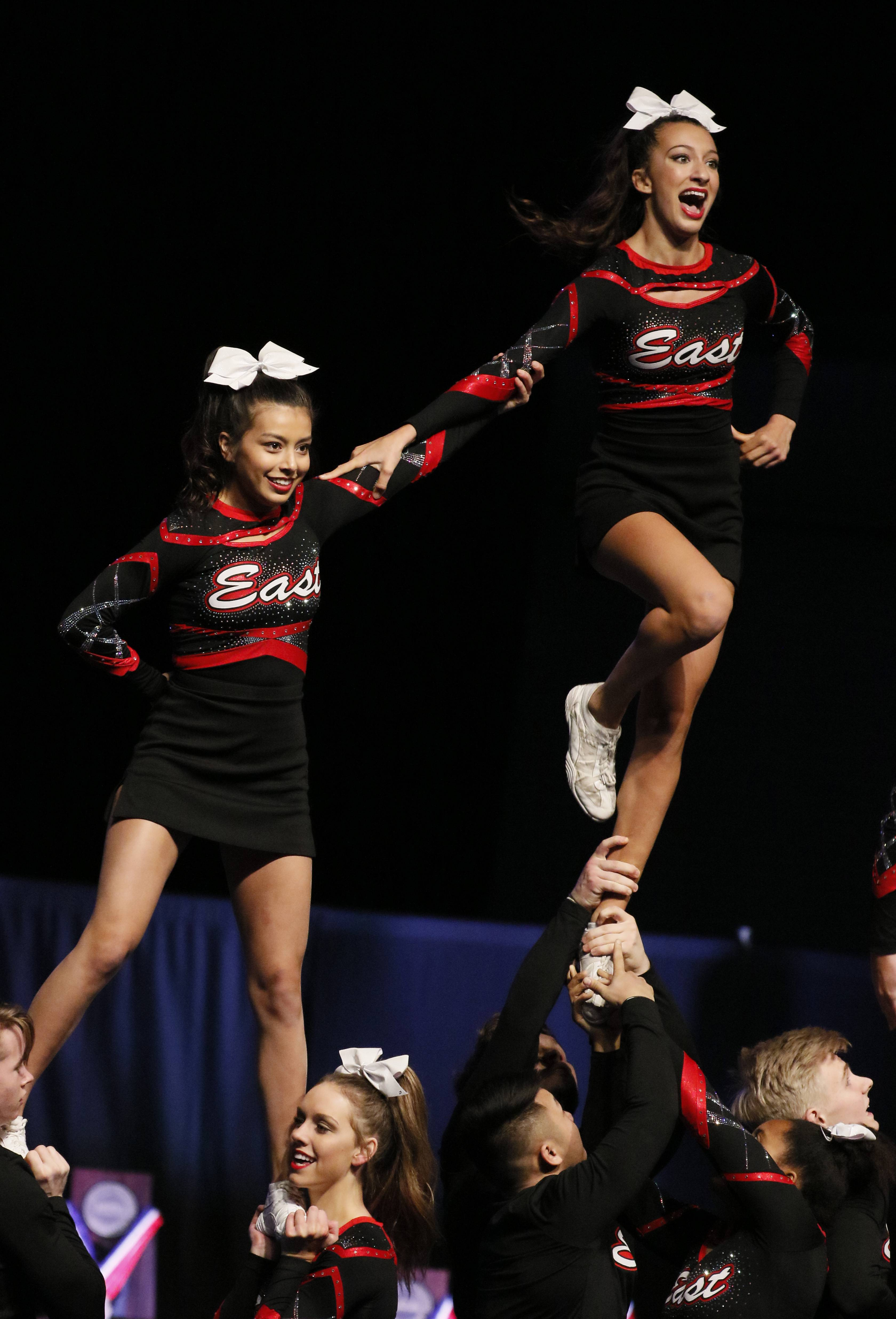 Glenbard East High School competes Friday during the preliminary round of the IHSA state cheerleading competition at the Grossinger Motors Arena in Bloomington.