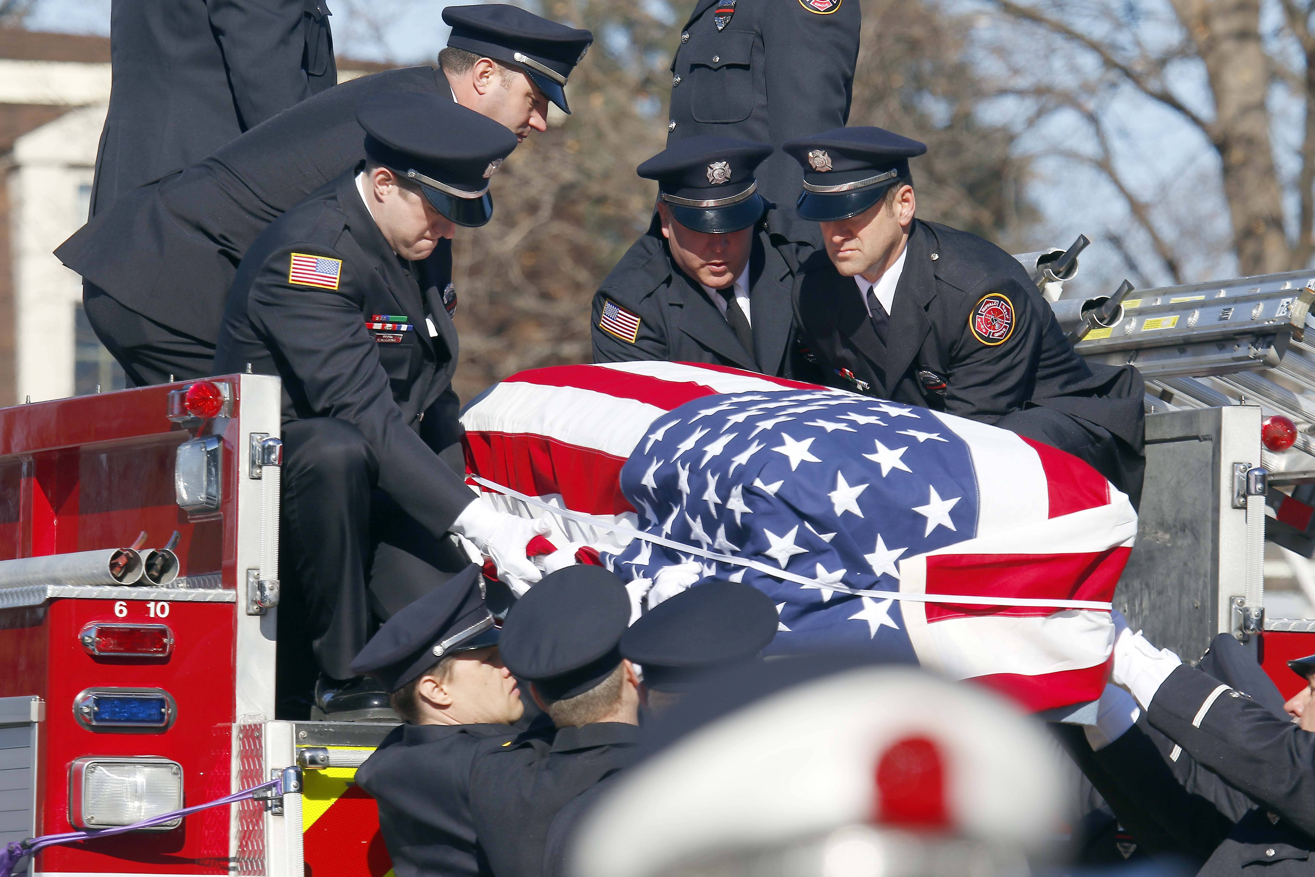Firefighters lower the body of Buffalo Grove firefighter/paramedic Kevin Hauber, 51, who died last weekend after a four-year battle with colon cancer.