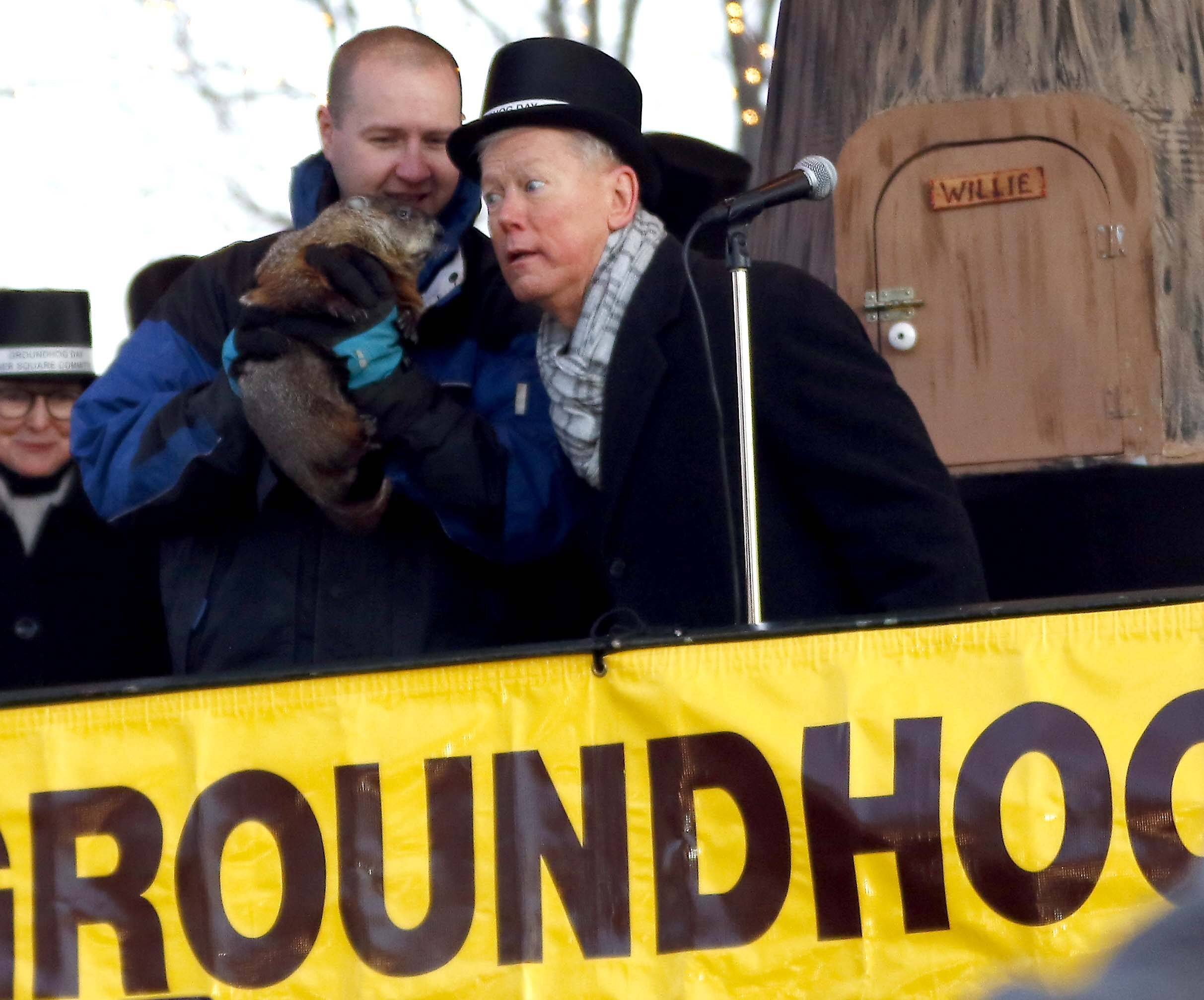Woodstock Mayor Brian Sager listens to Woodstock Willie, held by Mark Szafran. Willie saw his shadow after emerging from his slumber Friday during the annual Groundhog Day festivities in Woodstock.