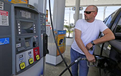 In this Tuesday, May 2, 2017, photo, Alex Uriarte pumps gas at a Chevron station in Miami. Chevron Corp. reports earnings, Friday, Feb. 2, 2018.